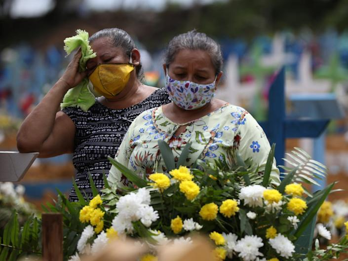 Women react during a collective burial of people that have passed away due to the coronavirus disease (COVID 19), at the Parque Taruma cemetery in Manaus, Brazil April 28, 2020. .JPG