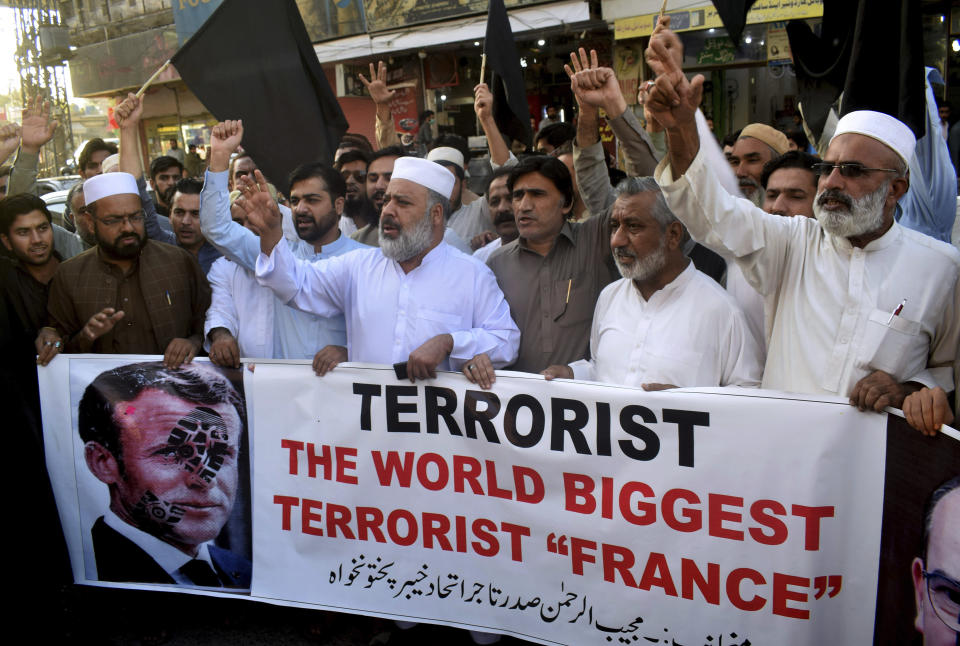 Pakistan traders hold a banner with a defaced picture of French President Emmanuel Macron during a protest against the publishing of caricatures of the Prophet Muhammad they deem blasphemous, in Peshawar, Pakistan, Monday, Oct. 26, 2020. Pakistan's Prime Minister Imran Khan said the French leader chose to encourage anti-Muslim sentiment and deliberately provoke Muslims by encouraging the display of blasphemous cartoons targeting Islam. (AP Photo/Muhammad Sajjad)