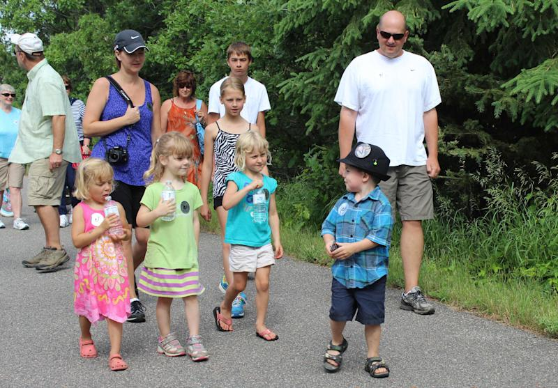 In this photo made Wednesday, June 26, 2013 in Dorset , Minn., Bobby Tufts, the small town's 4-year-old mayor, front, leads children and adults in the Ronald McDonald fundraising walk. Bobby was only 3 when he won election last year as mayor of Dorset (population 22 to 28, depending on whether the minister and his family are in town). Dorset, which bills itself as the Restaurant Capital of the World, has no formal city government. (AP Photo/Jeff Baenen)