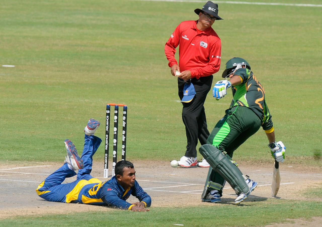 SHARJAH, UNITED ARAB EMIRATES - FEBRUARY 22:  Priyamal Perera of Sri Lanka fields of his own bowling during the ICC U19 CWC super league qualifier 4 match between Pakistan and Sri Lanka played at the Sharjah cricket stadium on February 22, 2014 in Abu Dhabi, United Arab Emirates.  (Photo by Pal Pillai-IDI/IDI via Getty Images)