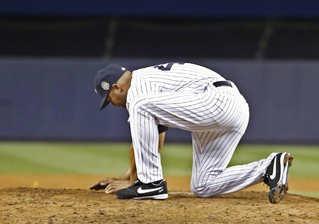CORRECTS WINNING TEAM TO RAYS - New York Yankees relief pitcher Mariano Rivera gathers dirt from the mound after his final appearance in a baseball game at Yankee Stadium, Thursday, Sept. 26, 2013, in New York. The Rays won 4-0. (AP Photo/Kathy Willens)