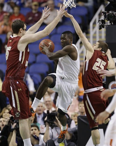 Miami's Durand Scott, center, is trapped by Boston College's Joe Rahon, right, and Andrew Van Nest, left, during the first half of an NCAA college basketball game at the Atlantic Coast Conference tournament in Greensboro, N.C., Friday, March 15, 2013. (AP Photo/Gerry Broome)