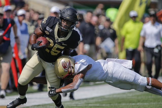 Wake Forest running back Kenneth Walker III, left, carries the football as Elon defensive back Cole Coleman tackles him in the first half of an NCAA college football game in Winston-Salem, N.C., Saturday, Sept. 21, 2019. (AP Photo/Nell Redmond)