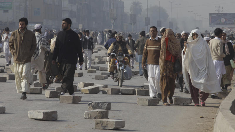 People thread their way through concrete slabs used by protesters to block the main highway in Peshawar, Pakistan, to protest against the lack of transport on Monday, Jan. 2, 2012.  Countrywide protests and strikes caused disruption across many cities as people protested against price hikes in gas and petroleum products.  (AP Photo/Mohammad Sajjad)