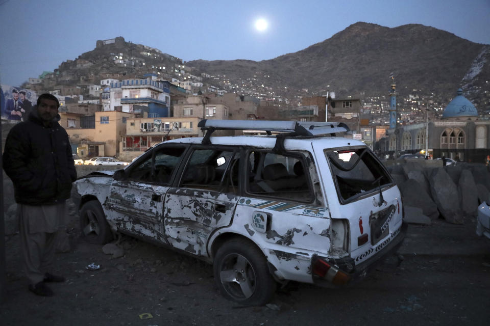 An Afghan man inspect the site of a bomb attack in Kabul, Afghanistan, Monday, Dec. 28, 2020. (AP Photo/Rahmat Gul)