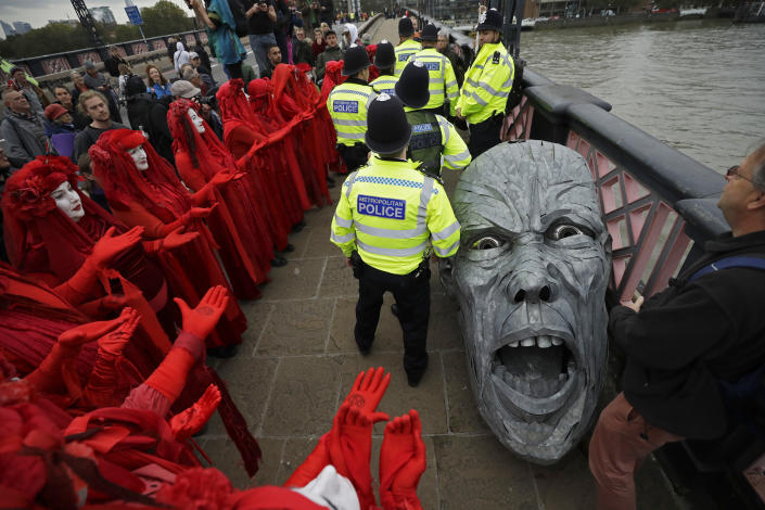 Environmental protestors gather around the head of a statue confiscated by police on Lambeth bridge in central London Monday, Oct. 7, 2019. (Photo: Matt Dunham/AP)
