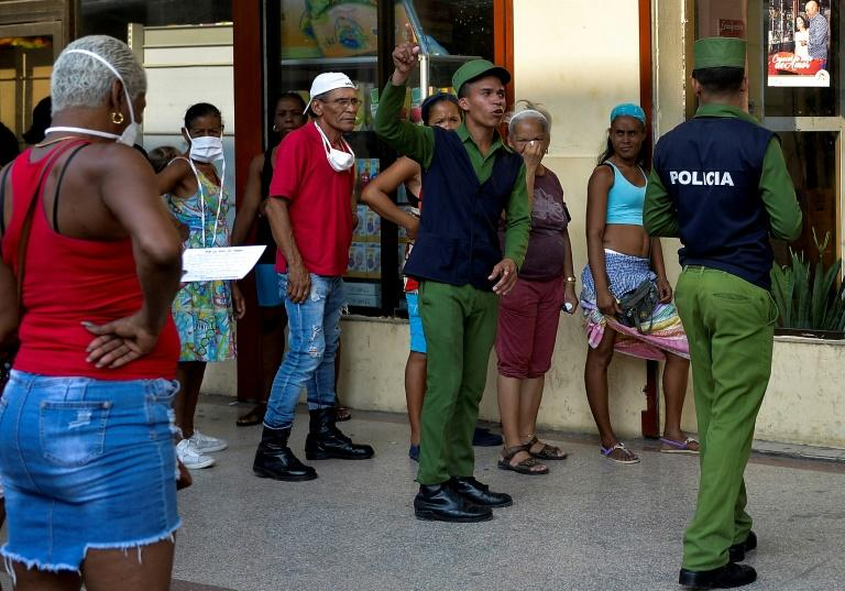 Police stand guard to ensure a minimum of distance between shoppers lined up in Havana (AFP Photo/YAMIL LAGE)