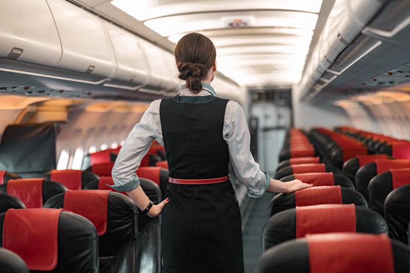 Adult flight attendant doing her obligations in airplane stock photo. Airways concept
