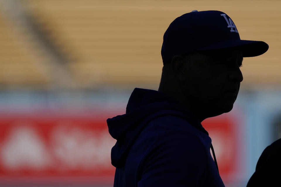 Los Angeles Dodgers manager Dave Roberts is silhouetted during batting practice before Game 4 of the baseball team's National League Division Series against the San Francisco Giants, Tuesday, Oct. 12, 2021, in Los Angeles. (AP Photo/Marcio Jose Sanchez)