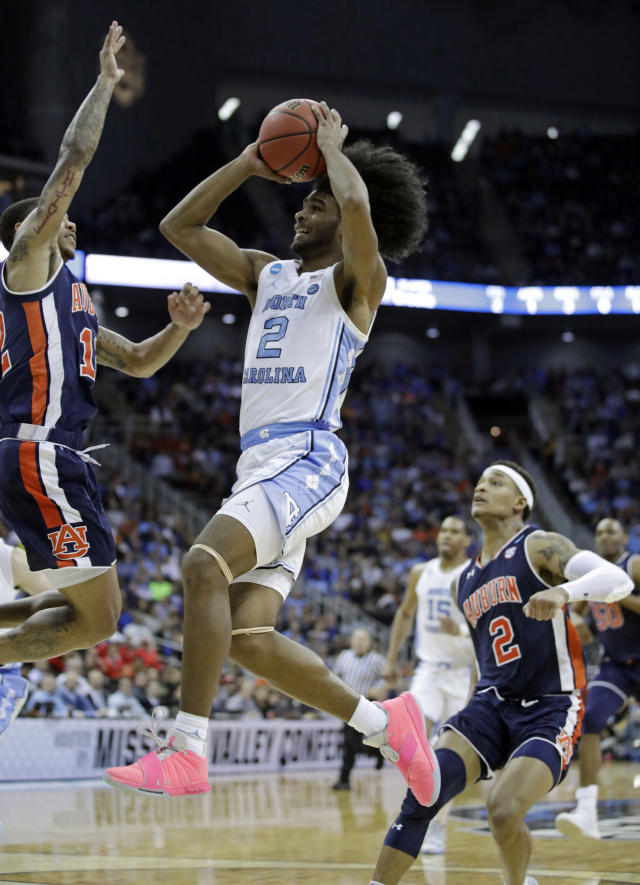 FILE - In this March 29, 2019, file photo, North Carolina's Coby White (2) heads to the basket as Auburn's J'Von McCormick, left, and Bryce Brown (2) defend during the first half of a men's NCAA tournament college basketball Midwest Regional semifinal game, in Kansas City, Mo. Ja Morant, Darius Garland and Coby White make up a clear top tier of point guards in next week's NBA draft, though one has barely played in the past year. (AP Photo/Charlie Riedel, File)