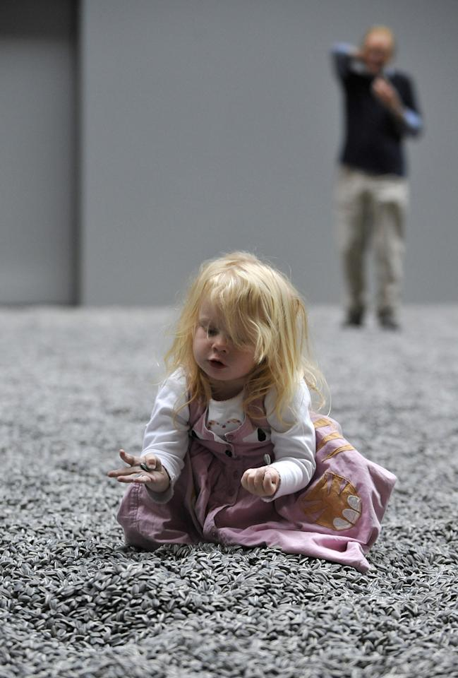Two-year old Connie Sweet plays inside the art installation 'Sunflower Seeds' by Chinese artist Ai Weiwei in London, Monday, Oct. 11, 2010. The specially commissioned art piece takes the form of a field of sunflower seeds inside the Turbine Hall at Tate Modern gallery, made of over 100 million handmade unique porcelain replicas of sunflower seeds, made by Chinese Artist Ai Weiwei, and will run until May 2, 2011.