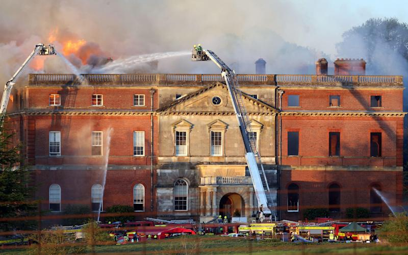 Firefighters battling the blaze at Clandon Park, near Guildford, Surrey, in April 2015 - Steve Parsons/PA