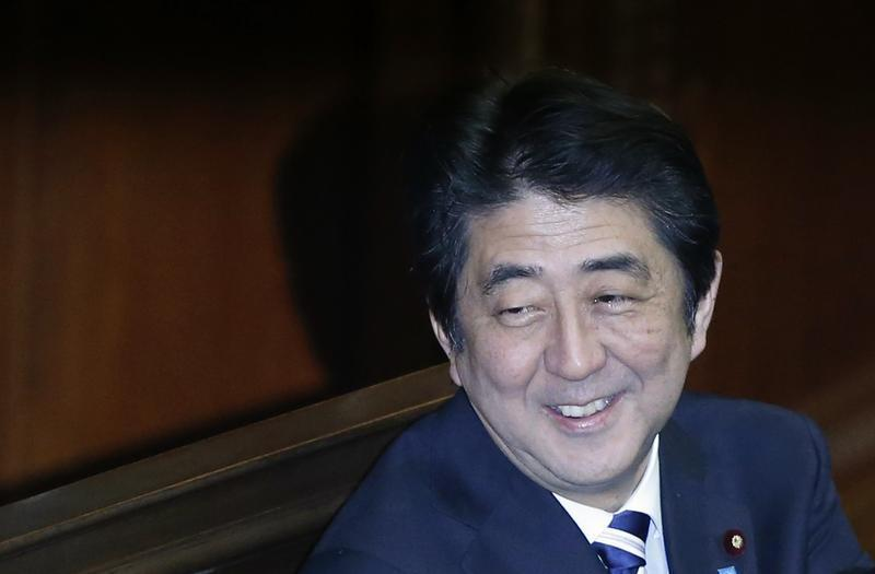Japan's PM Abe smiles during the Lower House plenary session of the parliament in Tokyo