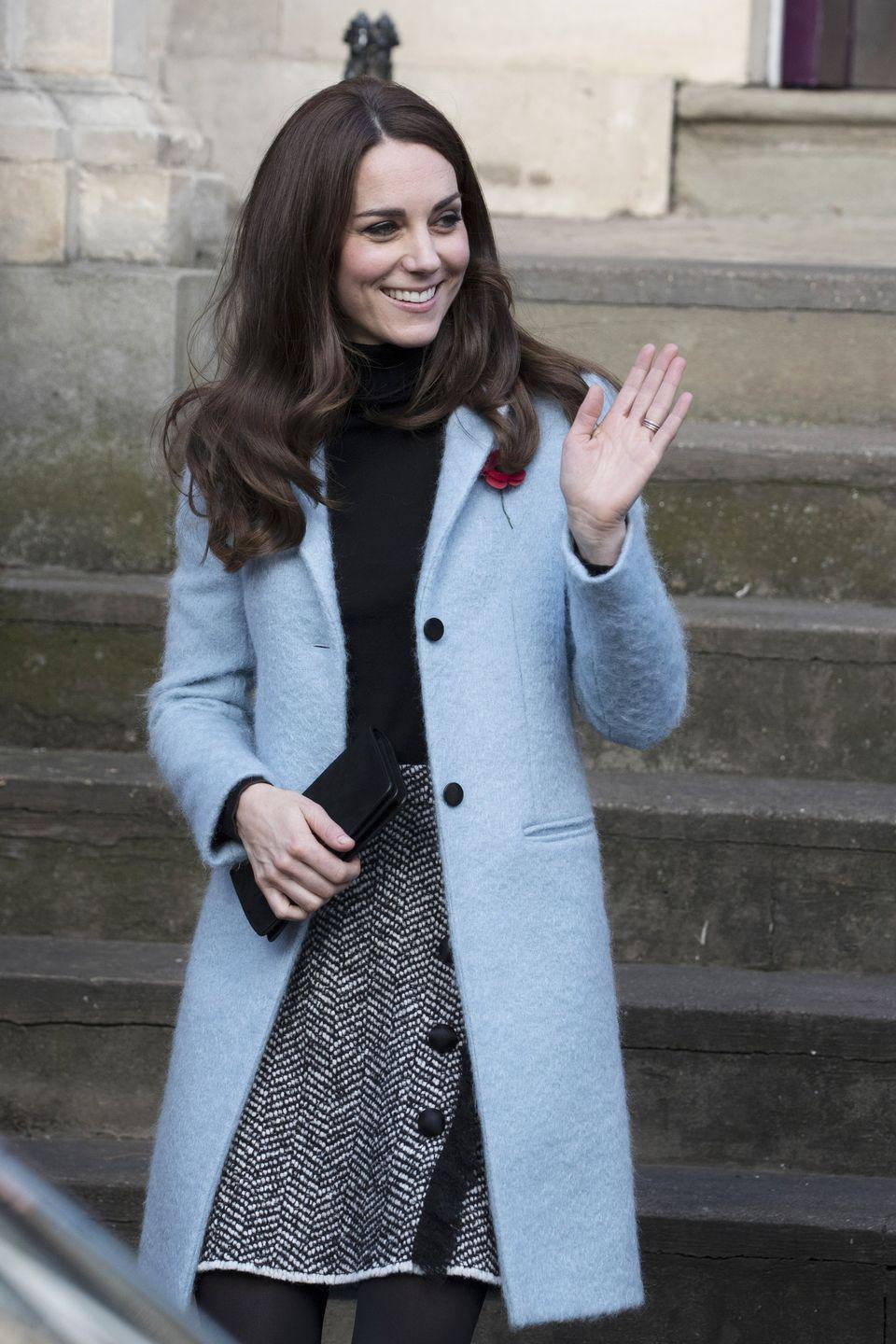 <p>In a light blue Mulberry coat, a black turtleneck, grey tweed Dolce & Gabbana skirt with button and fringe accents, a black leather clutch and black tights while visiting the Nelson Trust Women's Centre in Gloucestershire.</p>