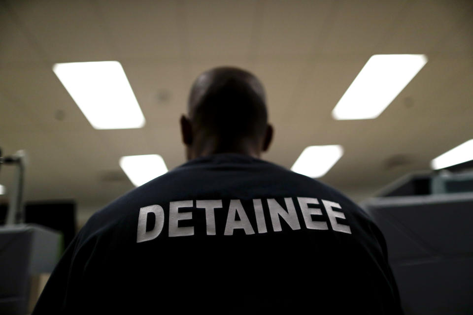 A detainee sits at the Otay Mesa Detention Center Wednesday, Aug. 23, 2017, in San Diego. The facility was at the center of the first big novel coronavirus outbreak at a U.S. immigration detention center in April 2020. (AP Photo/Gregory Bull)