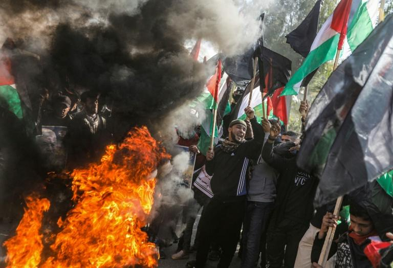 Palestinian demonstrators chant by flaming tires during a protest against US President Donald Trump's expected peace plan proposal in Gaza City (AFP Photo/MAHMUD HAMS)
