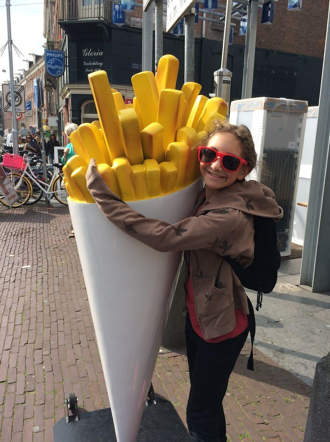 Sammi hugging a statue of french fries during a family trip to Amsterdam. (Photo: Debi Lewis)