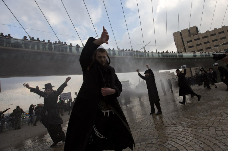 Police officers shoot a water canon at ultra-Orthodox Jewish men during their demonstration in Jerusalem, Thursday, Feb. 6, 2014. Israeli police said thousands of ultra-Orthodox Jews are blocking highways across the country to protest plans to enlist them into the military. (AP Photo/Sebastian Scheiner)