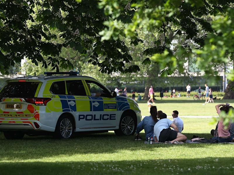 Police officers in a patrol car move sunbathers on in Greenwich Park: PA