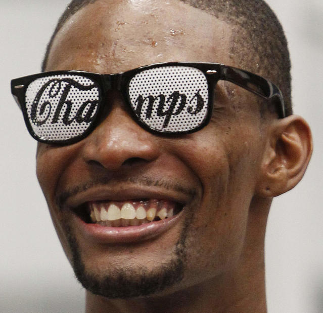 The Miami Heat's Chris Bosh enjoys a moment in the locker room after Game 5 of the NBA finals basketball series against the Oklahoma City Thunder, Friday, June 22, 2012, in Miami. The Heat won 121-106 to become the 2012 NBA Champions. (AP Photo/Wilfredo Lee)