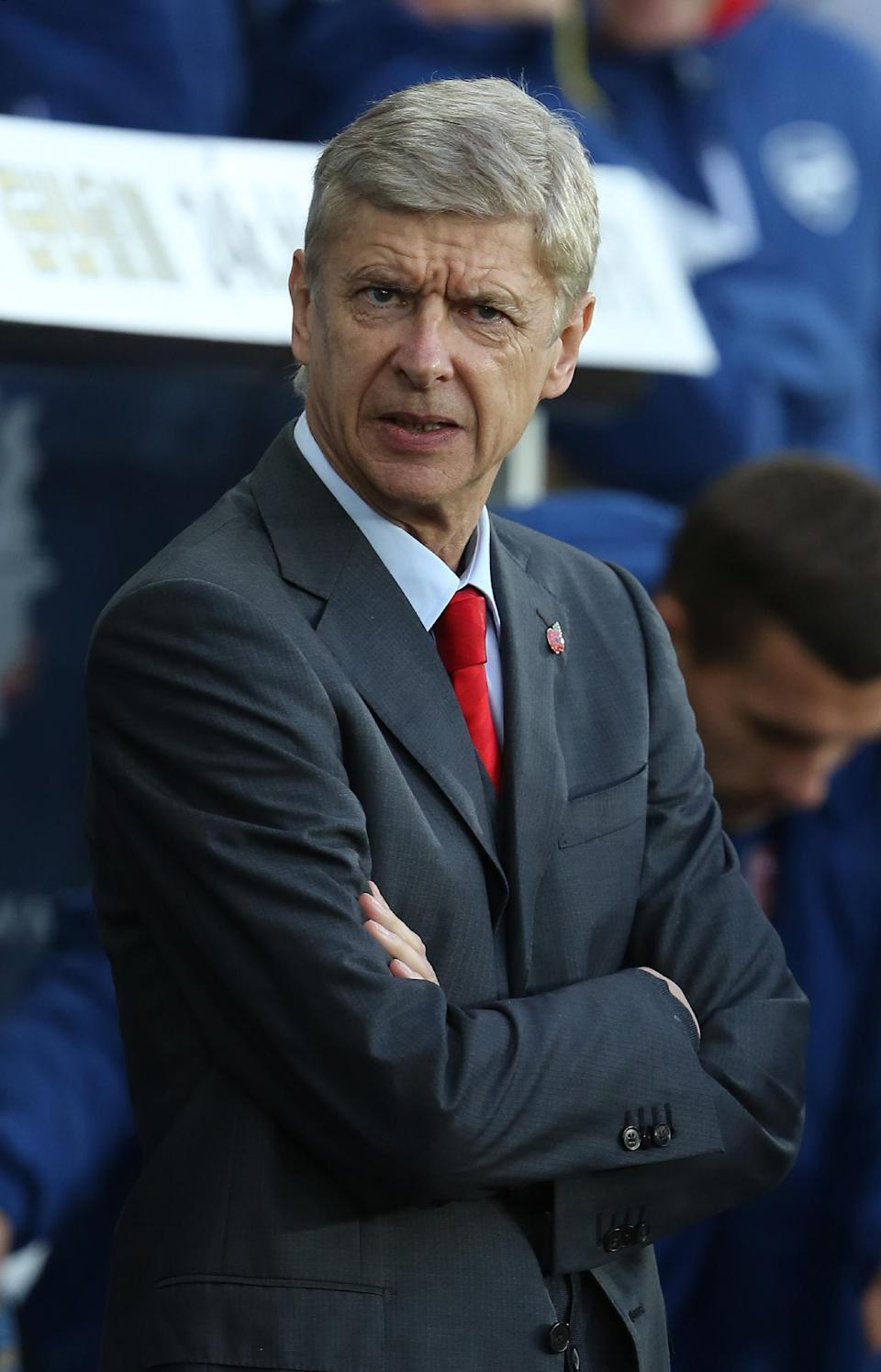 Arsenal's French manager Arsene Wenger enters the dugout at the beginning of the English Premier League football match between Swansea City and Arsenal in Swansea on November 9, 2014 (AFP Photo/Geoff Caddick)