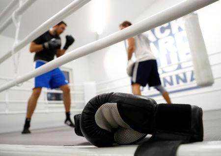 FILE PHOTO: Boxing gloves are seen as people warm up during a training session in the BackYard boxing club in Vienna, Austria September 19, 2017. REUTERS/Leonhard Foeger - RC12FBC09060