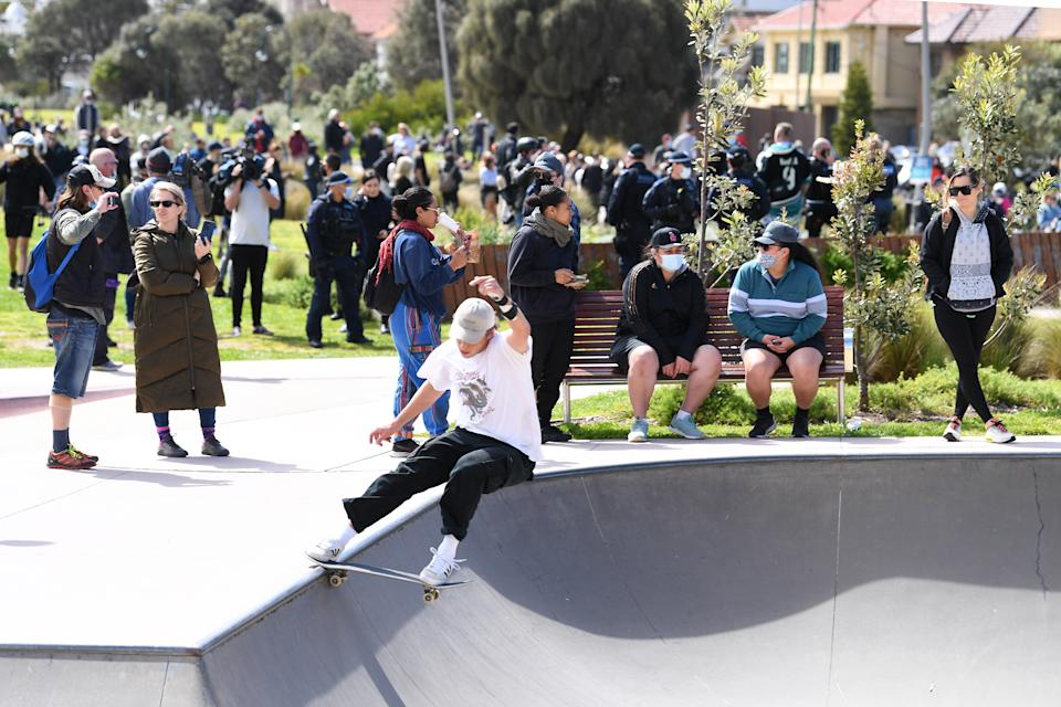 A skateboarder performs a frontside tail slide at the St Kilda skate park as protesters and Victorian Police converge into the area during a rally against mandatory Covid-19 vaccinations in St Kilda, Melbourne, Saturday, September 25, 2021. Source: AAP