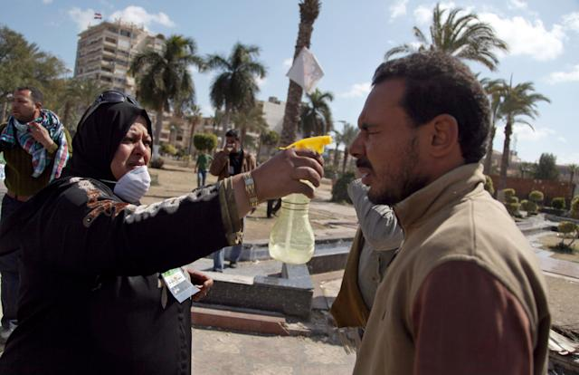 Egyptians react from tear gas fired by riot police during clashes near the state security building in Port Said, Egypt, Wednesday, March 6, 2013. Clashes between protesters and police have broken out in this restive Egyptian port city despite efforts by the military to separate the two sides. (AP Photo/Khalil Hamra)