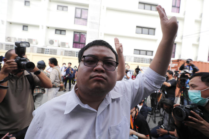 A pro-democracy activist, Parit Chiwarak, raises a three-fingers salute, a symbol of resistance at Chana SongKhram police station in Bangkok, Thailand Monday, Nov. 30, 2020. The leaders of the pro-democracy protests reported themselves to the police for the additional charge of violating the lese majeste laws at Chanasongkram Police Station on Monday afternoon. (AP Photo/Sakchai Lalit)
