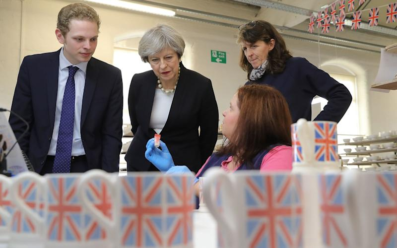Pottery worker Lisa Cooke demonstrates sponge decoration to British Prime Minister Theresa May and Stoke Central by-election candidate Jack Brereton, as they escorted by Emma Bridgewater (R) during a tour of the Emma Bridgewater pottery factory in Hanley - Credit: Reuters