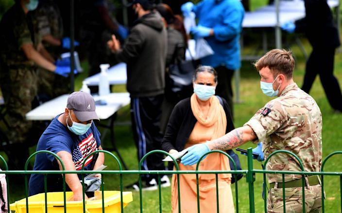 A member of the armed forces directs people to deposit their self-tests into a container in Spinney Hill Park in Leicester - AFP