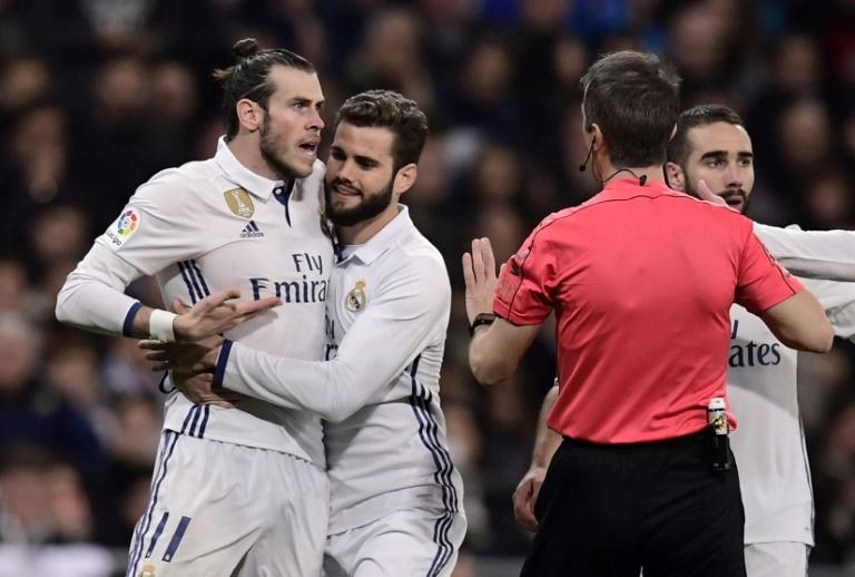 Real Madrid's forward Gareth Bale (L) argues with the referee as Real Madrid's defender Nacho Fernandez (2ndL) tries to stop on March 1, 2017