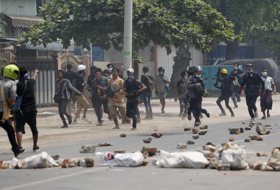 Demonstrators scatter as police fire tear gas during a protest against the military coup Saturday, March 27, 2021, in Mandalay, Myanmar. Myanmar security forces reportedly killed 93 people Saturday in the deadliest day since last month's military coup. (AP Photo)
