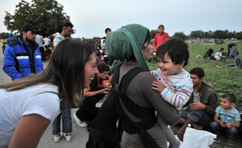 A woman (L) speaks with a migrant child as migrants and refugees wait for a bus to the Croatian-Hungarian border in the Croatian border village of Bapska, near the eastern town of Ilok, on September 23, 2015 (AFP Photo/Elvis Barukcic)