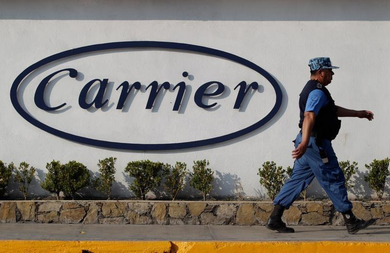 Private security guard walks past a logo of Carrier Corp outside the air conditioner plant, a unit of United Technologies Corp, in Santa Catarina