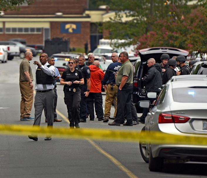 A Forsyth County Sheriff directs law enforcement officers on the scene at Mount Tabor High School Wednesday, Sept. 1, 2021 in Winston-Salem, N.C. Authorities say one student was killed in a shooting at a North Carolina high school and a suspect has been taken into custody.