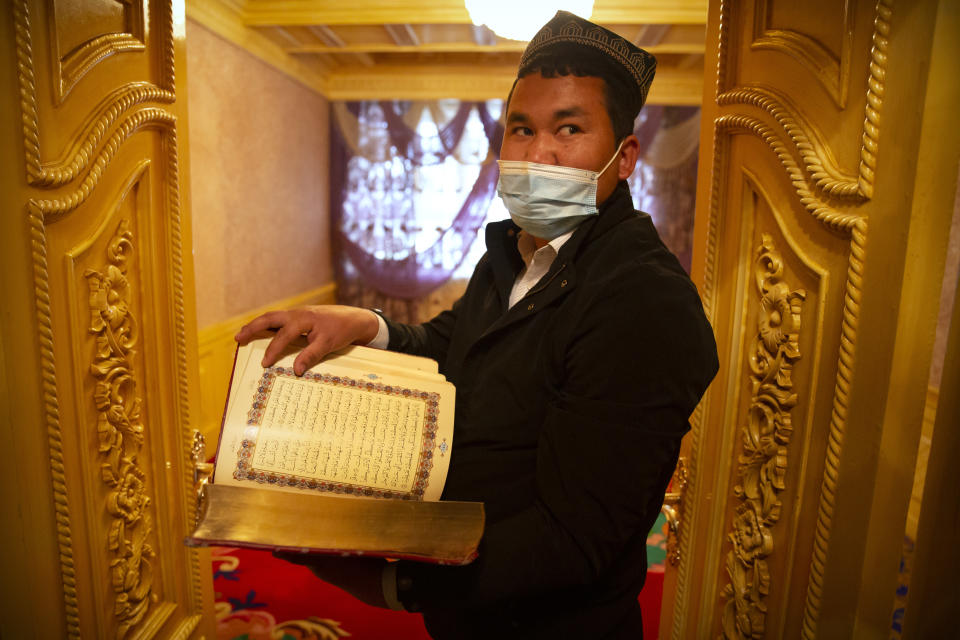 Tursunjan Mamat holds a copy of the Quran in the Arabic and Uyghur languages during a government organized visit for foreign journalists to his home in Aksu in western China's Xinjiang Uyghur Autonomous Region on April 20, 2021. Under the weight of official policies, the future of Islam appears precarious in Xinjiang, a remote region facing Central Asia in China's northwest corner. Outside observers say scores of mosques have been demolished, which Beijing denies, and locals say the number of worshippers is on the decline. (AP Photo/Mark Schiefelbein)