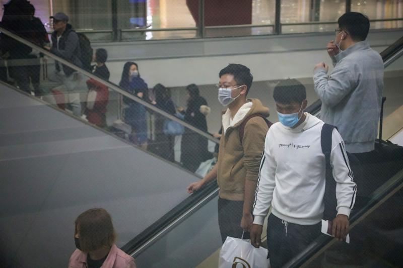 Travellers wearing face masks as a precautionary measure to protect against the possible spread of a SARS-like virus outbreak are seen behind a screen at Hong Kong International Airport ahead of the Chinese New Year in Hong Kong on January 23, 2020. - Hong Kong has turned two holiday camps, including a former military barracks, into quarantine zones for people who may have come into contact with carriers of the Wuhan virus, officials announced on January 23. The international financial hub has been on high alert for the virus, which has killed 17 people since the outbreak started in central China. (Photo by VIVEK PRAKASH / AFP) (Photo by VIVEK PRAKASH/AFP via Getty Images)