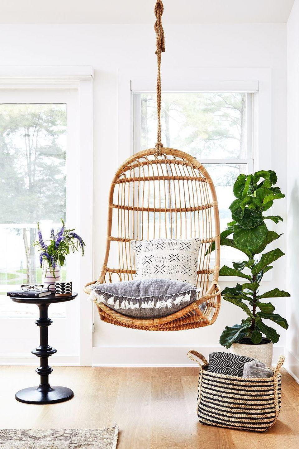 <p>Ideal for a small space, a rattan swing chair and petite end table make for the perfect lounge area. </p>