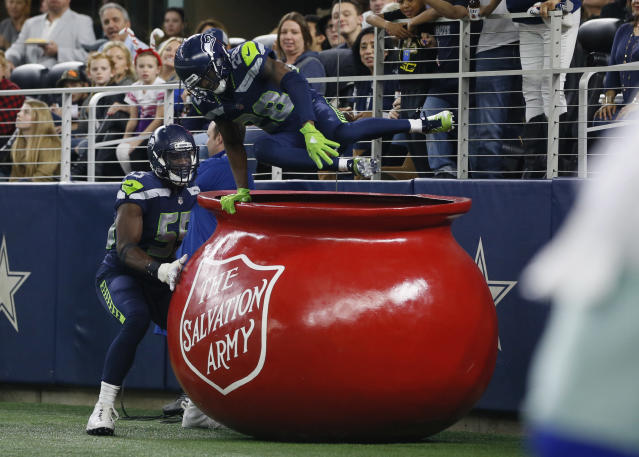 Seattle Seahawks cornerback Justin Coleman (28) jumps out of a Salvation Army kettle with defensive end Frank Clark (55) after returning an interception for a touchdown against the Dallas Cowboys in the third quarter at AT&T Stadium. Tim Heitman-USA TODAY Sports