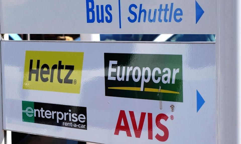 A sign showing the way to car hire companies at an airport.