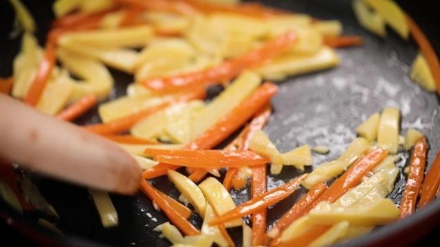 stir frying bamboo shoots and carrots in a pan