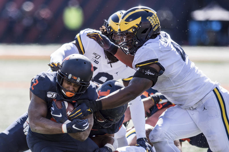 Illinois' Reggie Corbin (2) holds tight to the ball as he is hit by Michigan's Michael Danna (4) in the second half of an NCAA college football game, Saturday, Oct. 12, 2019, in Champaign, Ill. (AP Photo/Holly Hart)