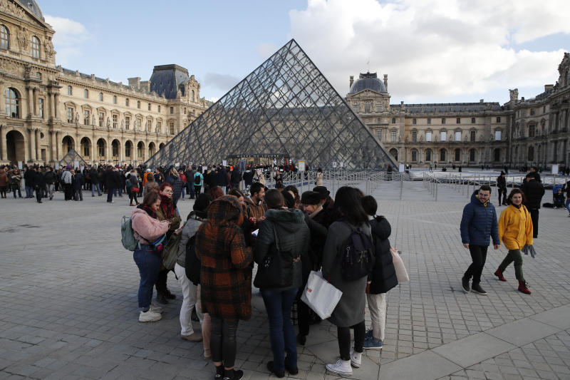 Visitors wait as striking employees demonstrate outside the Louvre museum Friday, Jan. 17, 2020 in Paris. Paris' Louvre museum was closed Friday as dozens of protesters blocked the entrance to denounce the French government's plans to overhaul the pension system. (AP Photo/Francois Mori)