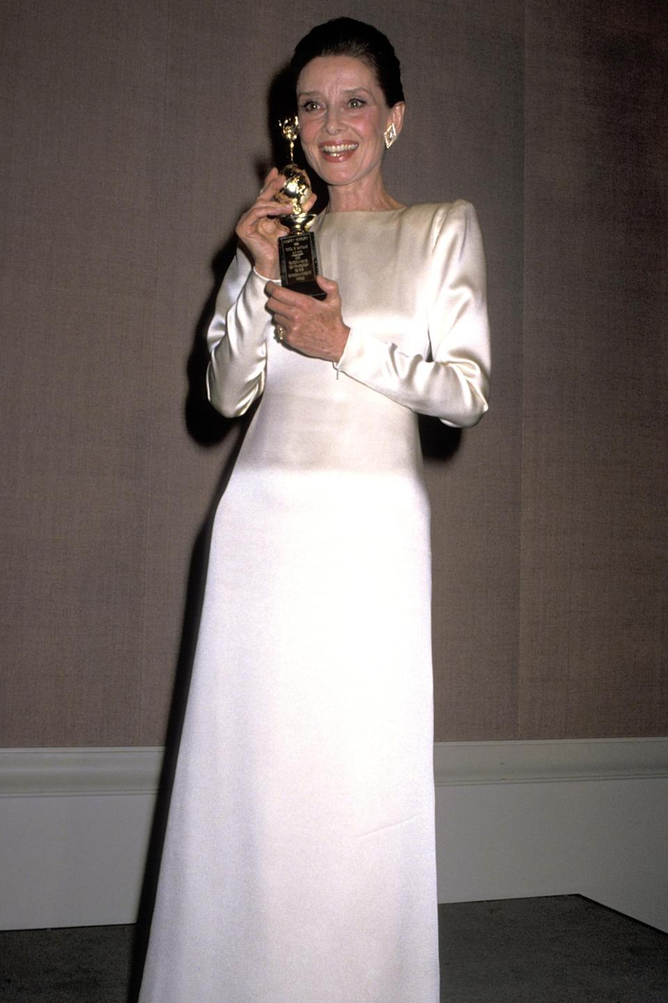 """<h2>1990</h2><br>Simply put, Audrey Hepburn could do no wrong — a fact proven by this remarkable ensemble.<br><br><em>Audrey Hepburn in a white satin gown. </em><span class=""""copyright"""">Photo: Ron Galella/WireImage.</span>"""