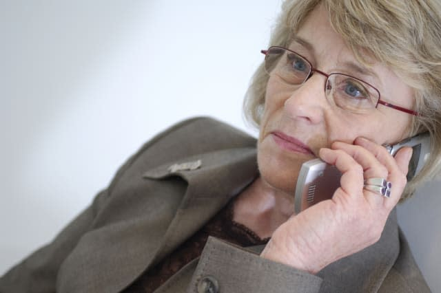 mature businesswoman talking on mobile phone looking concerned