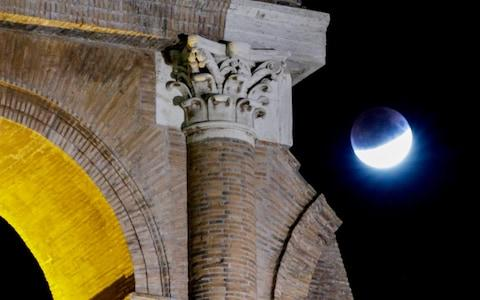 July's full moon, also known as the Thunder Moon, is seen over the Colosseum during a partial lunar eclipse, in Rome, late Tuesday, July 16, 2019. - Credit: Andrew Medichini/AP