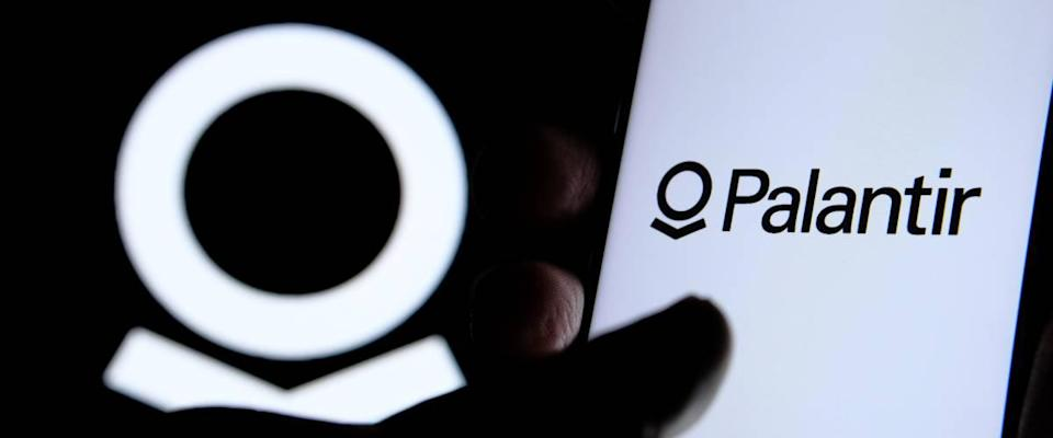 Palantir company logo on the screen of smartphone, finger touching it and the blurred Palantir logo on the background.