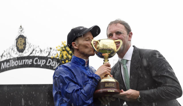 Jockey Kerrin McEvoy, left and English trainer, Charlie Appleby, right celebrate after winning the Melbourne Cup with Cross Counter at Flemington Racecourse in Melbourne, Australia, Tuesday, Nov. 6, 2018. (AP Photo/Andy Brownbill)