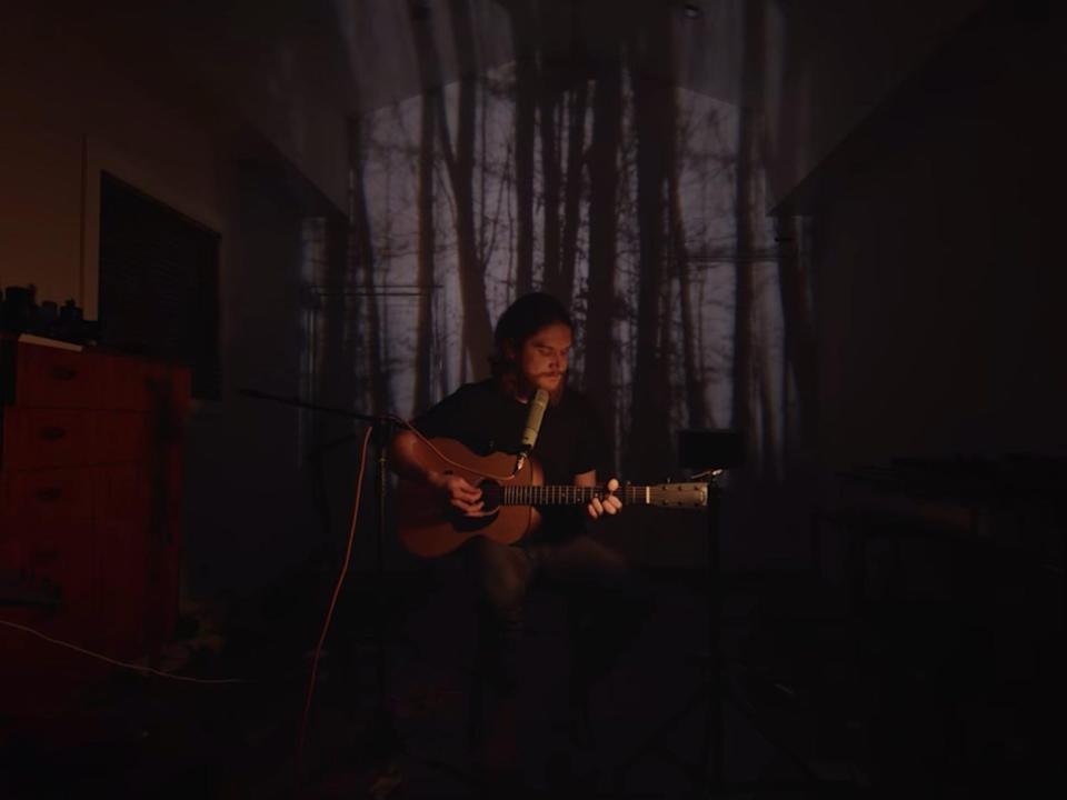 A man (Bo Burnham) playing an acoustic guitar while sitting in front of a projection of a forest background.